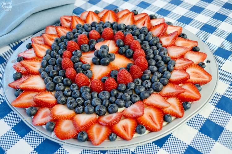 This easy sugar cookie fruit pizza is topped with fresh berries and a sweet glaze. Loaded with strawberries, blueberries and raspberries, this dessert pizza makes the perfect summer treat or patriotic dessert for 4th of July, Labor Day or Memorial Day!