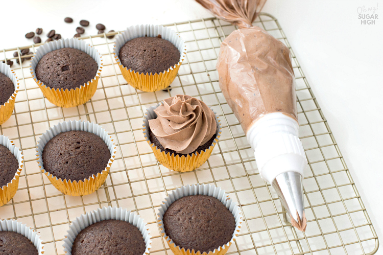 Adding mocha frosting to chocolate cupcakes.